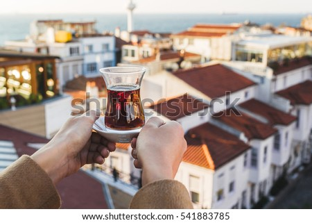 Hand holding a cup of traditional Turkish tea illuminated and transparent by the warm evening sunlight. Sunset teatime in Istanbul