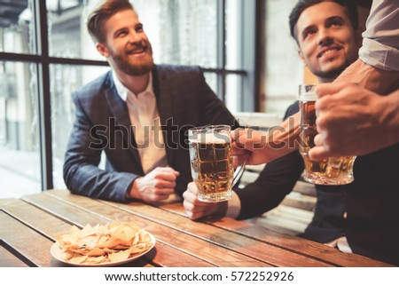 Handsome businessmen are drinking beer  talking and smiling while resting at the pub