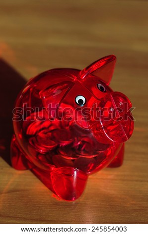 Red piggy bank with coins inside on a wooden table