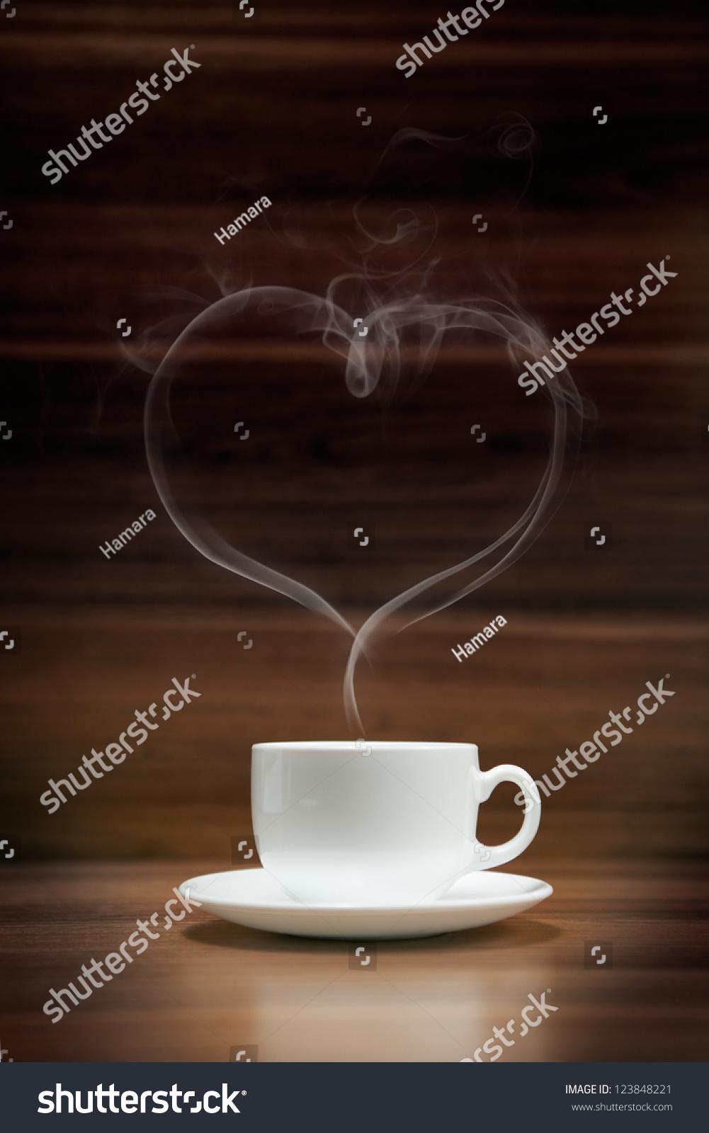 一杯咖啡和心形的烟黑木头背景