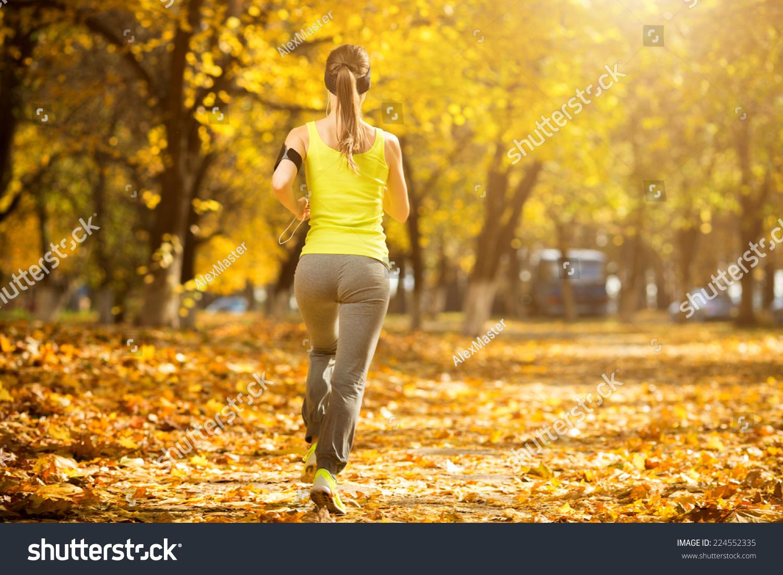 跑慢跑在公园在秋天晴朗明亮的光线背景.图片