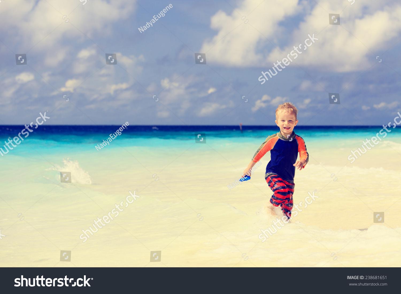 快乐的小男孩砂热带海滩上运行