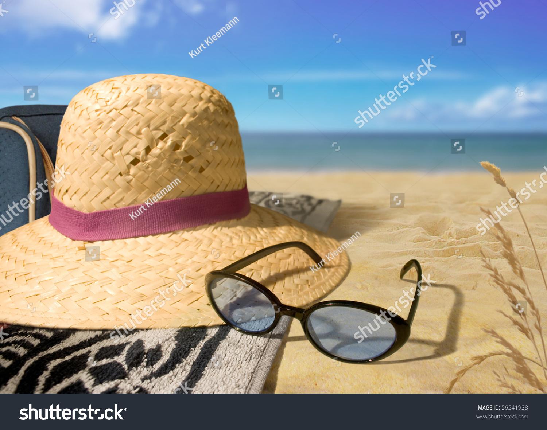 海滩的一天稻草帽子和太阳镜在海滩上图片