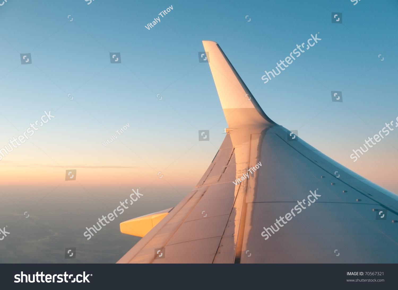 飞机的机翼在日落的背景天空