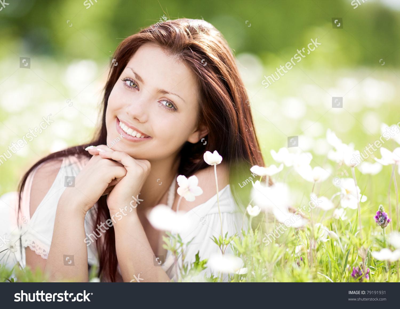年轻漂亮的黑发女人放松白色花朵的草地上一个温暖的图片