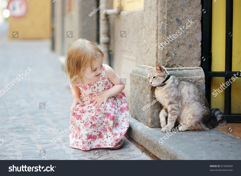 可爱的快乐的小女孩和一只猫在户外